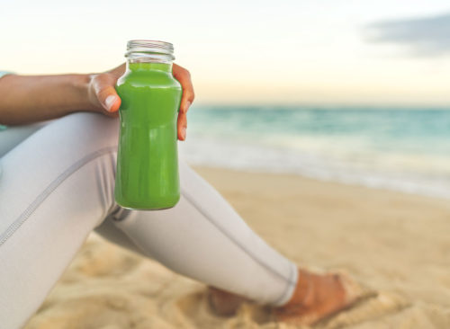 Woman holding green juice beach
